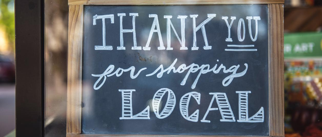 "closeup of chalkboard sign reading ""Thank you for shopping local"""