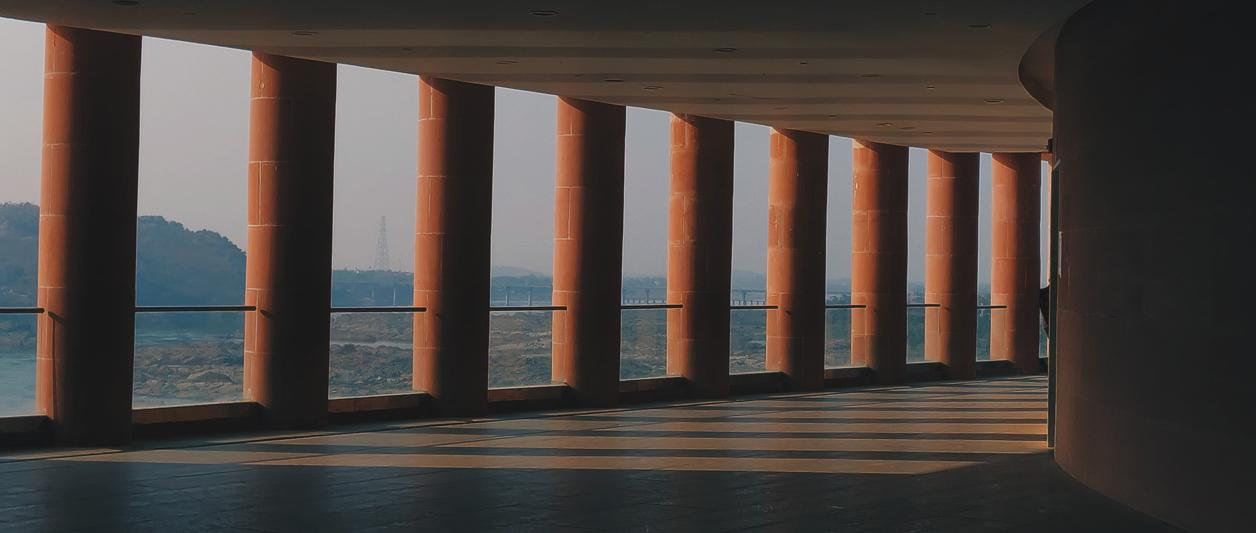 photo of row of pillars with sunlight pouring between them