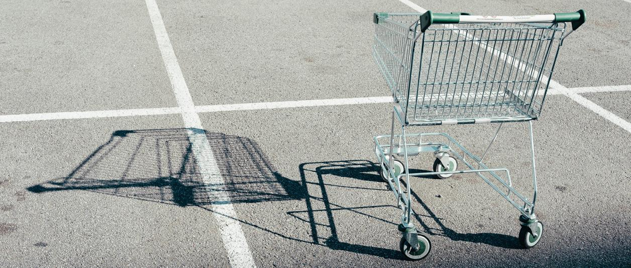 photo of wire shopping cart abandoned in a parking lot
