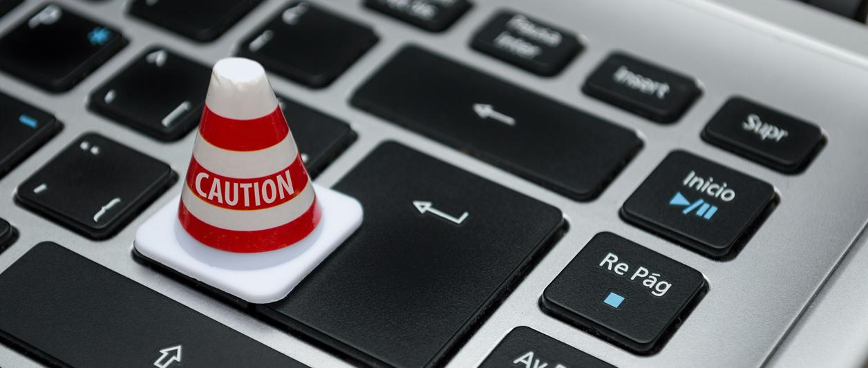 closeup of miniature caution cone sitting on laptop keyboard